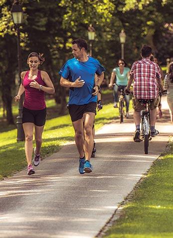 Menschen im Park joggen und fahren Rad